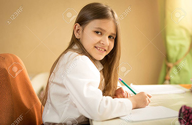 Portrait of smiling girl in white shirt sitting behind desk and